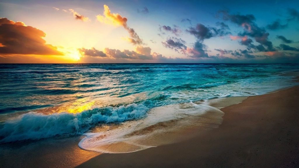 ocean with sunrise and sand