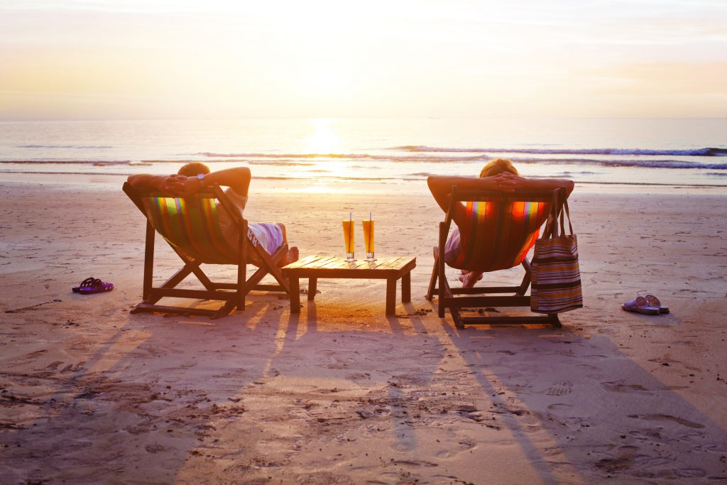 couple relaxing on beach watching the sunset and waves