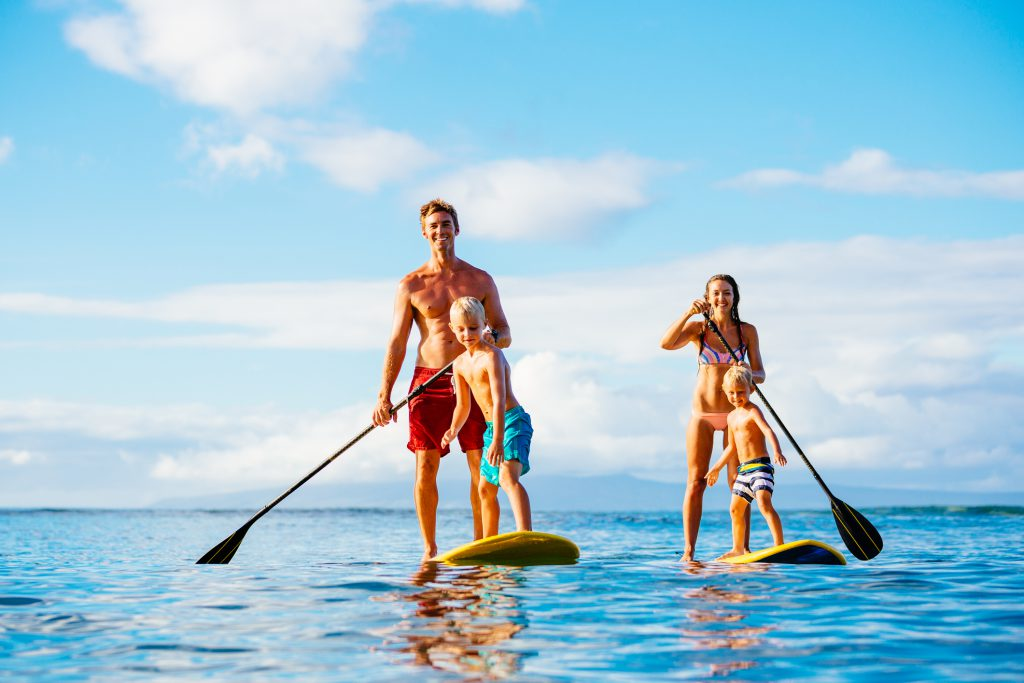 Man in swimsuit, young boy in swimsuit, young woman in swimsuit, young boy in swimsuit, on paddleboads on ocean holding oars, blue skies, light clouds,