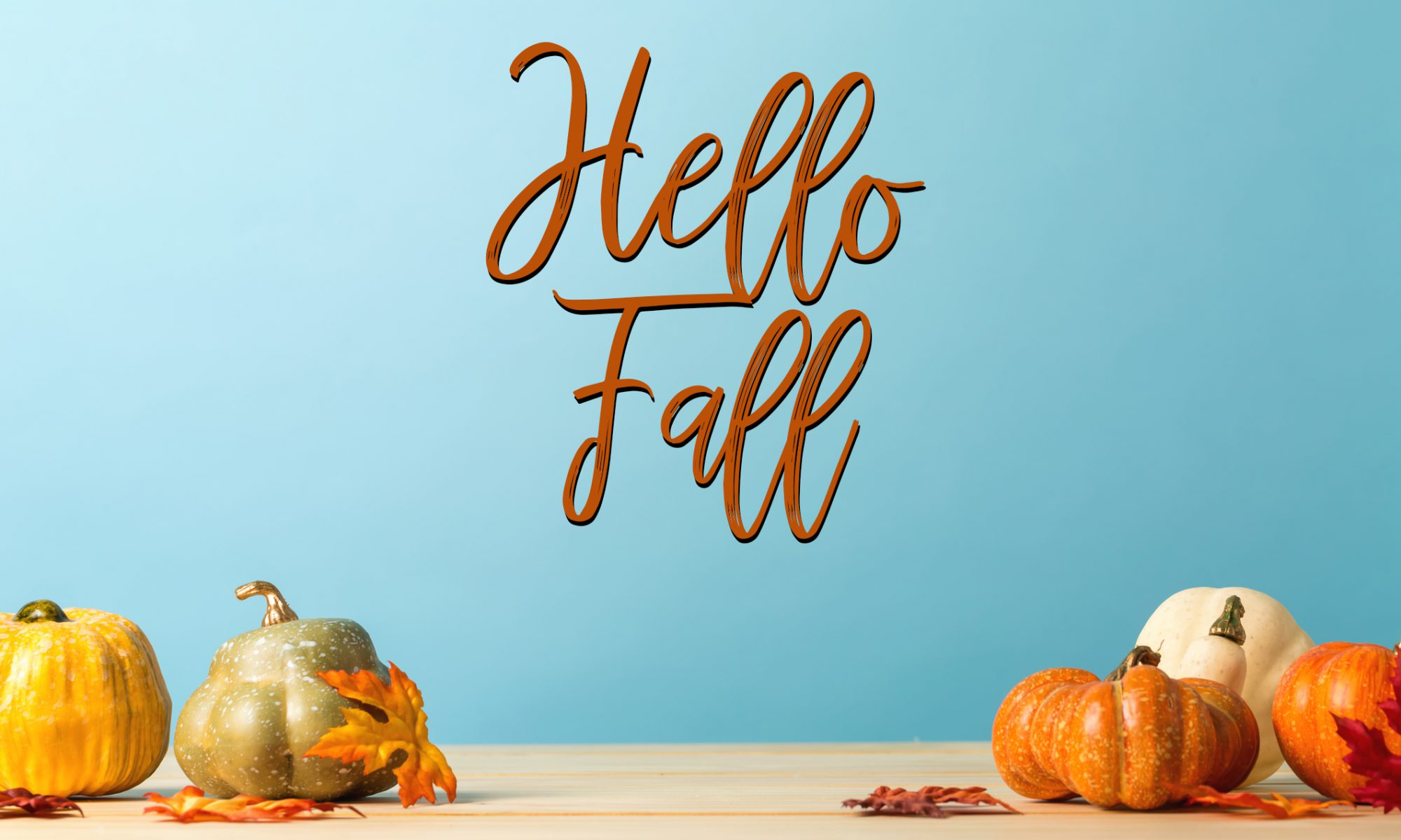 Collection of autumn pumpkins on a blue background with Hello Fall in orange and black